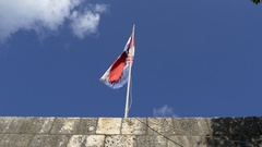 Croatian tattered flag hanging down pole over stone entrance of Ston Stock Footage