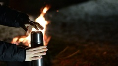 Woman pours hot tea from a thermos into a cup. Cold winter night. Stock Footage