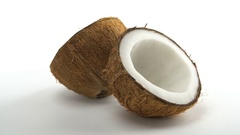 Ripe tropical coconut split in two halves rotating on a white background Stock Footage