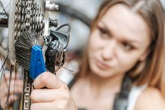 Attentive hardworking technician brushing the chain of the bicycle Stock Photos