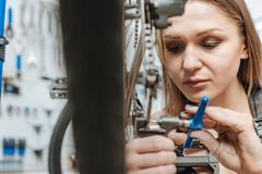 Hardworking young technician fixing the pedal of the bicycle Stock Photos