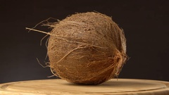 Ripe tropical coconut rotating on wooden table against black background Stock Footage