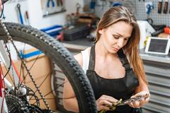 Attentive female mechanic wiping fuel oil on the cogwheel Stock Photos