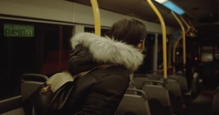 A young girl rises up from chair and goes out of the bus. Night bus Stock Footage