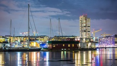 Time Lapse of houseboat marina and tower block building at night Stock Footage