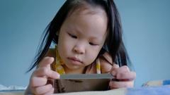 Girl watching cartoons via smart phone Stock Footage