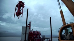 A small yellow crane lifts large pieces of red metal. backlit, silhouette Stock Footage