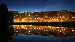 Calm city river at night. Railroad station in the background, traffic passing by Stock Footage