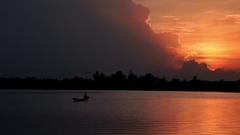 Fantastic sunset on a Malian lake, A fisherman on a canoe paddling Stock Footage
