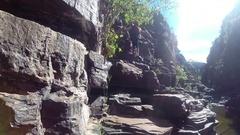 Hiker walking on rock ledge in Joffre Gorge in Karijini NP Stock Footage