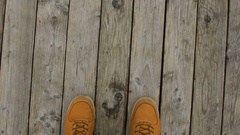 Walking on a pier at the beach, POV shot of a man with yellow shoes Stock Footage