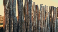 Wooden fence from big trunks, in the background sundown with sunflare Stock Footage