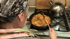 Grandmother cooks noodles Stock Footage