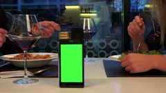 A man and a woman sit at a table and eat, a smartphone with a green screen in Stock Footage