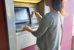 Close up of woman inserting card to atm machine Kuvituskuvat