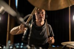 Male musician playing drums and cymbals at concert Kuvituskuvat