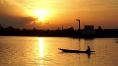 An African fisherman rows with an oar with a fantastic sunset, on a canoe Stock Footage