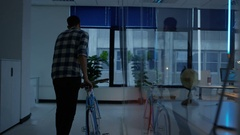 4K Businessman walking in to creative office with bicycle in the morning Stock Footage