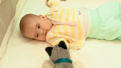 Cute newborn baby playing with a plush toy in his crib Stock Footage