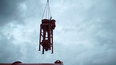 A huge metal funnel is moved by crane. backlit silhouette. About industry Stock Footage