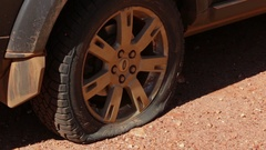 Flat tire on a 4x4 on gravel road Stock Footage