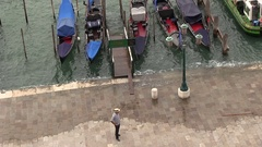 Gondolier waiting of better weather in Venice in Italy Stock Footage