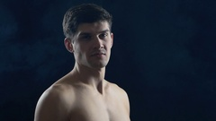Young shirtless man standing in dark, with smoke around him Stock Footage