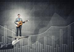 Businessman on metal tray playing acoustic guitar against graphs background Stock Photos