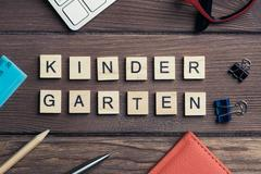 Office stuff and Kinder Garden phrase collected with letters on wooden surface Stock Photos