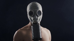 Man in gas mask standing in dark, with smoke around him Stock Footage