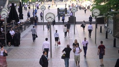 Commuters and clocks at Canary Wharf London UK Stock Footage