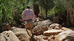 Female hiker walking along dry creek bed into Emma Gorge Stock Footage