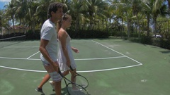 A young couple walking together to the tennis courts while on vacation. Stock Footage