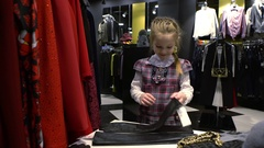 5 years old girl trying on gloves in a clothing store. Stock Footage
