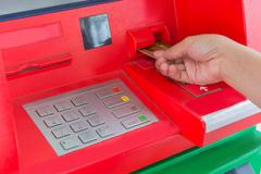Hand insert credit card to ATM bank cash machine for withdraw money Kuvituskuvat