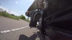 Motorcycle leans hard for corner and shifts gear in straight stretch go pro Stock Footage