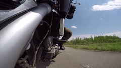 Motorcycle cool go pro angle of front end looking backwards on race track Stock Footage
