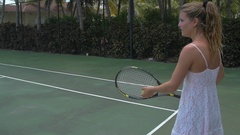 A young woman playing tennis with her boyfriend while on vacation, slow motion. Stock Footage