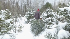 Man drags christmas tree through snow with his dog follow cam 4k Stock Footage