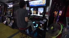 Young man plays DrumMania, a drumming music video game in Bangkok Stock Footage