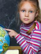 Girl - a child of seven years on the geography lesson near  globe  the world Stock Photos
