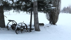 Snow falling on antique mowing machine under pine tree Stock Footage