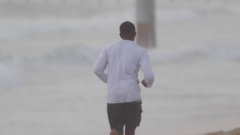 A young man runner getting a workout running in the sand on the beach. Stock Footage