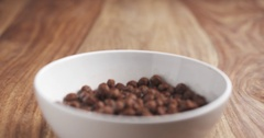 Chocolate cereal balls with milk in white bowl on wood table slide movement Stock Footage