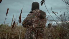 Hunter calls geese from a marsh Stock Footage