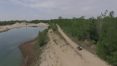 Aerial quad atv riding along water in sandy pit Stock Footage
