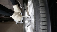 Man unscrews the wheel of a car Stock Footage