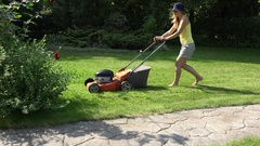 Young girl mowing green grass lawn with orange push mower. 4K Stock Footage