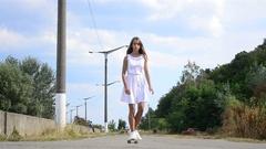 Beautiful teenager girl riding a skateboard towards camera Stock Footage