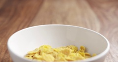 Corn flakes in white bowl on wooden table slide back Stock Footage
